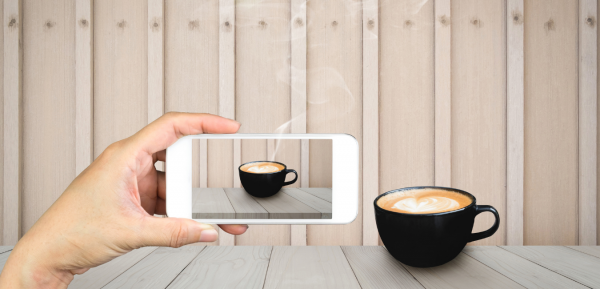 Taking photo on mobile phone of coffee cup